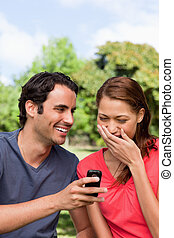 Woman laughing at something being shown to her on her friend's ph