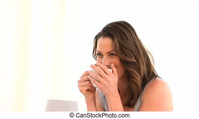 Woman laughing before drinking a coffee