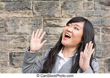 Woman laughing by a stone wall