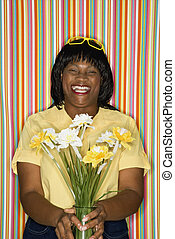Woman laughing holding flowers.