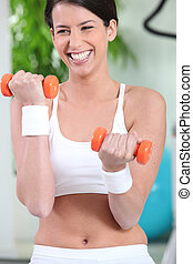 Woman laughing while lifting dumbbells