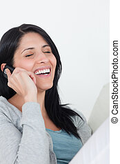 Woman laughing while phoning