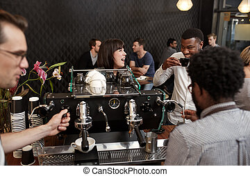 Woman laughing with African friend at counter of coffee shop