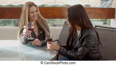 Woman laughing with friend over wine