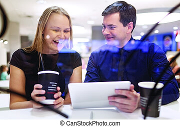 Woman laughs as man shows tablet - Woman laughs as man shows...