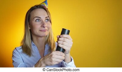 woman launches confetti on a yellow background slow motion