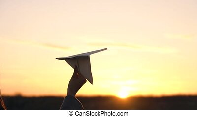 Woman launches paper airplane against sunset background....