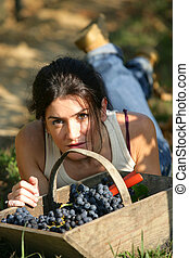 Woman laying down with basket of grapes