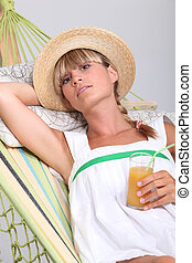 Woman laying in hammock drinking fruit cocktail