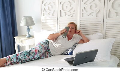 Woman laying on a bed using laptop