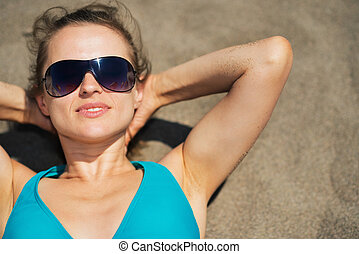 Woman laying on beach sand