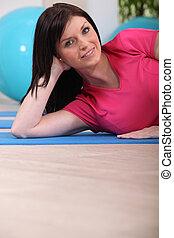 Woman laying on gym mat