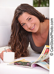 Woman laying on sofa with cup of coffee and magazine
