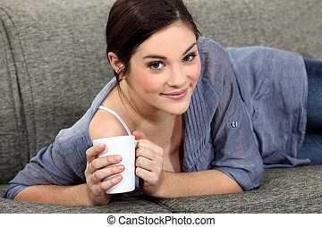 Woman laying on sofa with mug of coffee