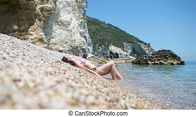 Woman laying on the beach enjoying summer holidays looking...
