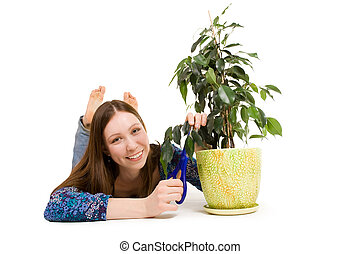 Woman laying on the floor cutting plant