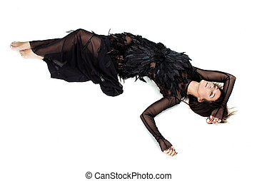 Woman laying on the floor in black feathers dress