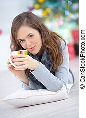 Woman laying on the floor with a cup of coffee
