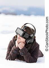 woman lays in the snow, with vr glasses