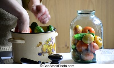 Woman lays tomatoes and cucumbers in jars. Home canning for the winter
