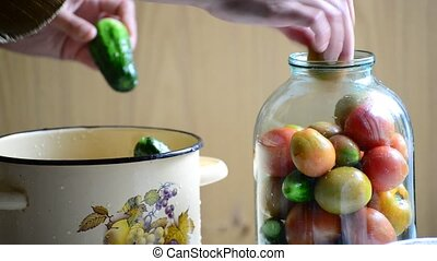 Woman lays tomatoes and cucumbers in jars. Home canning for  winter