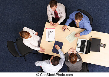 Five Businesspeople gathered around a table for a meeting, brainstorming. Aerial shot taken from directly above the table.