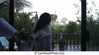 Woman Leading Man To Balcony To See Tropical Woods Morning...