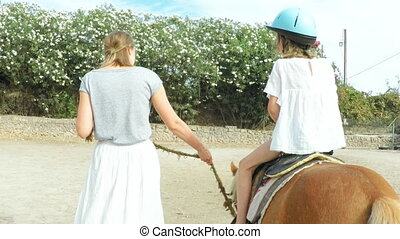 Woman leading pony with little girl.