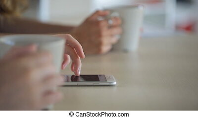 Woman leafs news feed on your smartphone lying on a table, next to other hands hold a cup of tea.