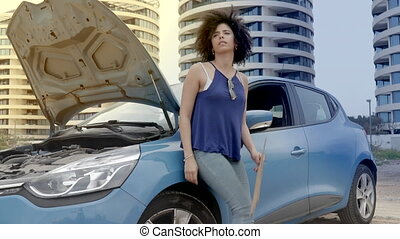Woman lean on car and holding help sign