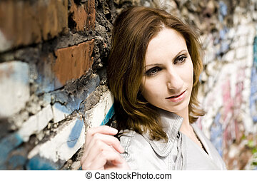 Woman leaning against a concrete wall