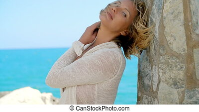 Woman Leaning Against Rock Wall By Windy Ocean