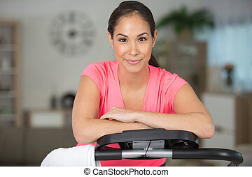 woman leaning on a fitness machine