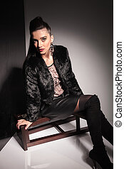 woman leaning on a stool while sitting on it