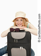 Woman leaning on a suitcase while sitting