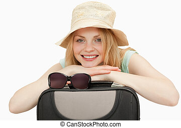 woman leaning on a suitcase while smiling