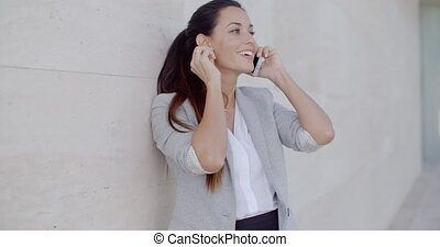 Woman leaning on a wall chatting on a mobile