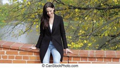 Woman leaning on bridge - Beautiful woman in black jacket...