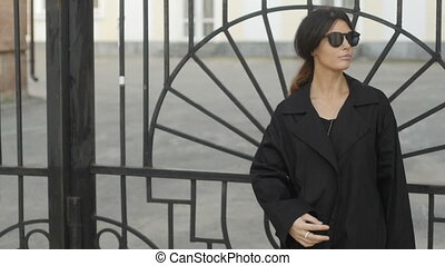 Woman leaning on gate - Charming woman in black jacket and...