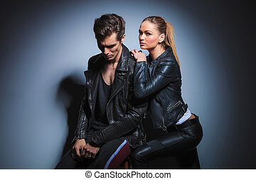 woman leaning on her man from behind while man in leather jacket is looking down