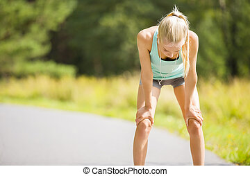 Woman leaning on knees and catch breath after stamina workout