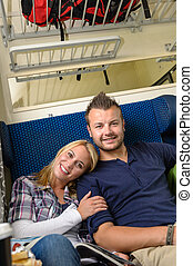 Woman leaning on man's shoulder in train