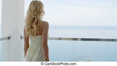 Woman Leaning on Ocean Front Balcony Railing - Rear View of...