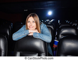 Woman Leaning On Seat At Movie Theater