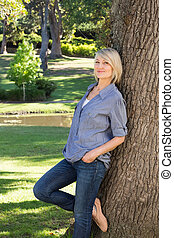 Woman leaning on tree trunk in park
