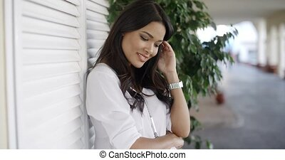 Woman Leaning On Wall And Looking At The Camera