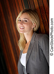 Woman leaning on wooden wall