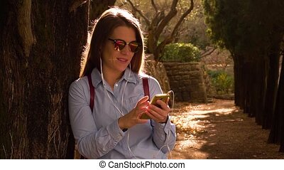 Woman Leans On A Tree And Put In Headphones