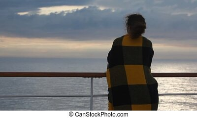 woman leans on handrail and looks at sea, then leaves