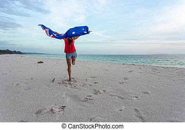 Woman leaping into the air with Australian Flag
